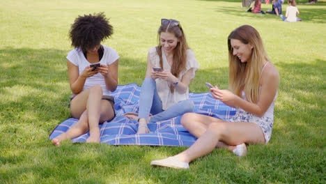 Women-using-smartphones-on-meadow