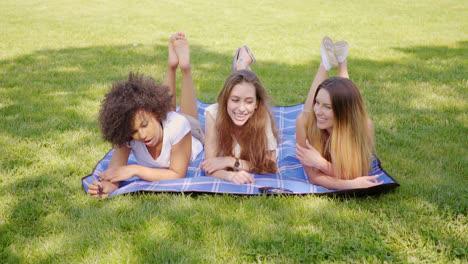 Happy-female-friends-lying-on-grass