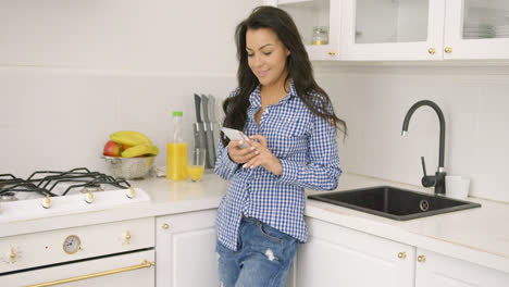 Young-casual-woman-with-smartphone-in-kitchen
