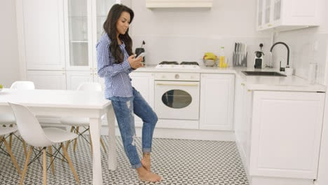 Young-barefoot-woman-using-phone-in-kitchen
