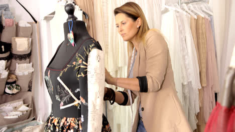 Female-dressmaker-using-mannequin-in-parlour