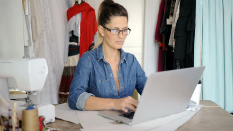 Female-tailor-using-laptop-at-work