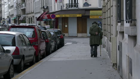 France-Old-man-walking-down-sidewalk-with-cane