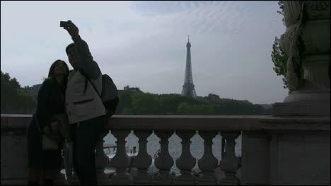 Francia-Pareja-Tomando-Fotos-Con-La-Torre-Eiffel-En-Segundo-Plano-