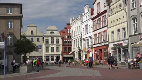 Germany-Wismar-people-walking-past-buildings