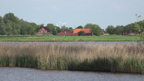 Germany-farmstead-and-wind-turbines-beyond-lake-and-reeds