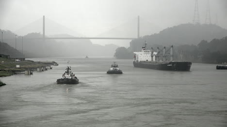 Panama-cargo-ship-and-tug-boats-in-canal
