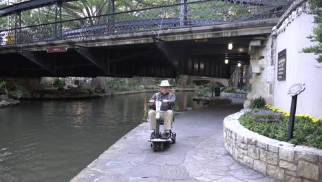 Hombre-De-San-Antonio-Paseos-En-Scooter-Bajo-El-Puente-Sobre-El-Río-Walk