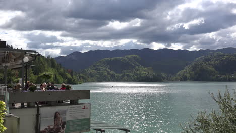 Slovenia-Bled-tourists-on-terrace-and-sun-on-Lake-Bled