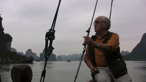Vietnam-Halong-Bay-man-on-boat-holds-line