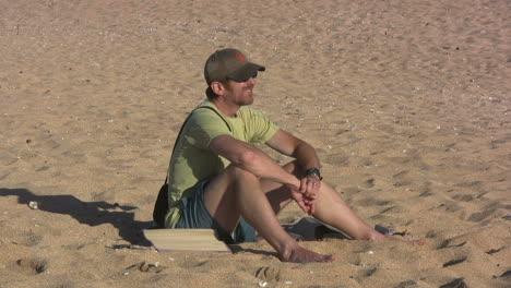 Hawaii-Kauai-man-seated-on-sandy-beach-2