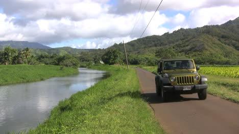 Kauai-A-jeep-on-a-road-by-a-stream
