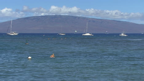Zooms-on-girl-and-sailboats-in-Hawaii