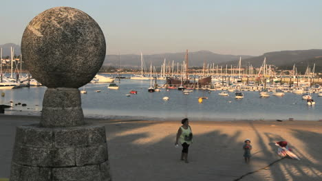 Spain-Galicia-Baiona-harbor-yellow-woman