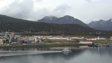 Argentina-Ushuaia-ship-passes-in-front-of-red-roof-buildings