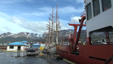 Argentina-Ushuaia-red-ship-with-masts-and-mountains