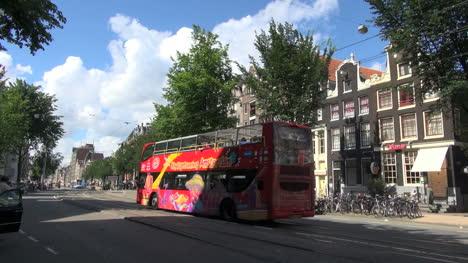 Netherlands-Amsterdam-red-tour-bus-bikes-under-gable