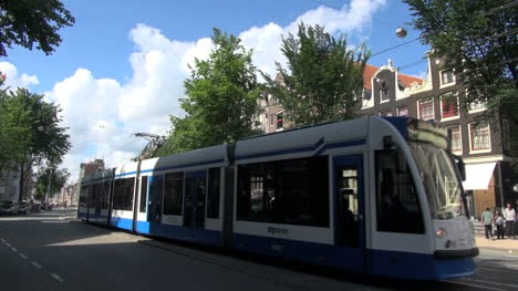 Netherlands-Amsterdam-blue-streetcar-passes-gabled-building