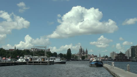 Netherlands-Amsterdam-dock-view-past-boats-to-church-spires