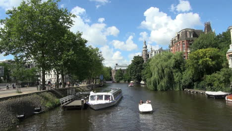Netherlands-Amsterdam-small-boat-and-tour-boat-on-canal