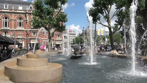 Países-Bajos-Amsterdam-Fuente-Surtidores-Y-Gran-Edificio-De-Ladrillo