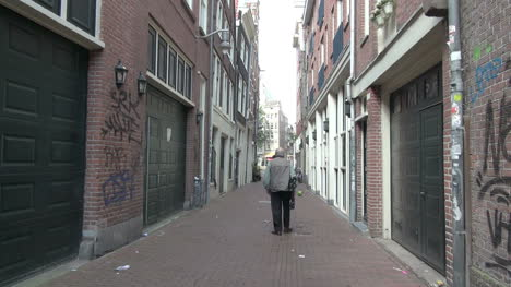 Netherlands-Amsterdam-man-walks-past-doors-and-graffiti-in-alley-2