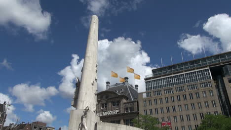 Netherlands-Amsterdam-dam-square-obelisk-and-flags-against-clouds-2