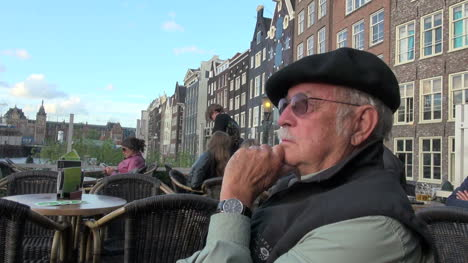 Netherlands-Amsterdam-houses-by-water-man-in-beret