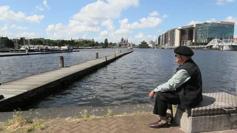 Netherlands-Amsterdam-canal-pier-man-in-beret