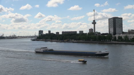 Netherlands-Rotterdam-boat-passes-barge-in-front-of-Euromast