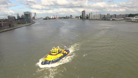 Netherlands-Rotterdam-bright-yellow-boat-in-murky-urban-river