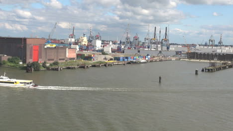 Netherlands-Rotterdam-waterside-cranes-and-passing-tour-boat