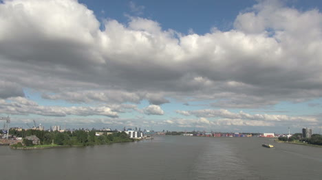 Netherlands-Rotterdam-wake-forms-in-river-below-clouds