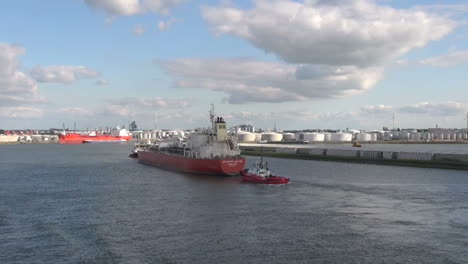Netherlands-Rotterdam-red-tanker-and-tug-pass-refinery-14a
