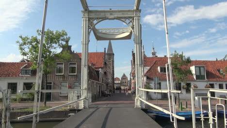 Netherlands-Edam-bikes-cross-canal-under-bridge-frame