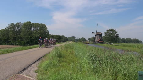 Netherlands-Kinderdijk-group-of-bikes-approach-past-windmill-20