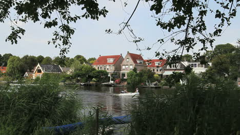 Netherlands-skiff-passes-canal-side-village-2