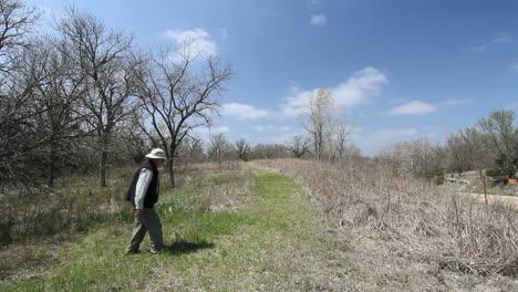 Kansas-Alcove-Spring-man-walks-near-bare-trees