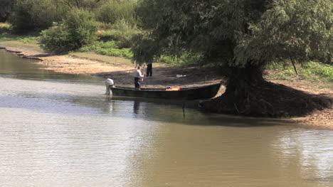 Romania-Danube-delta-fisherman-in-boat-by-bank-cx