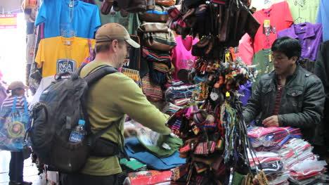 Peru-Cusco-man-in-cap-shops-at-vendor-booth