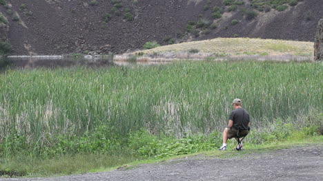 Washington-man-sits-near-marsh-and-gravel-slope