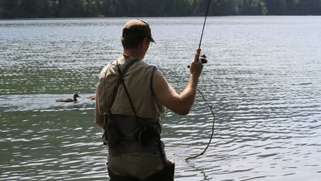 Canada-British-Columbia-Echo-Lake-reeling-in-while-ducks-swim-by-6