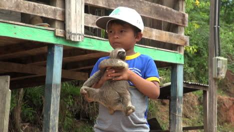 Brazil-Boca-da-Valeria-young-boy-holds-sloth