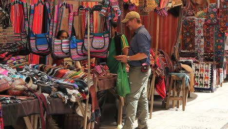 Peru-Pisac-market-man-barters-near-brightly-colored-bags-5