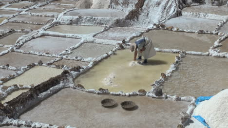 A-woman-works-to-pile-up-salt-in-a-salt-pan-in-the-Andes