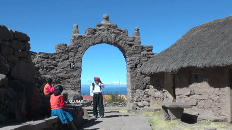 Peru-Taquile-man-under-stone-arch-and-thatch-roof-house-2