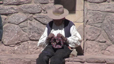 Peru-Taquile-man-weaves-by-hand-in-front-of-stone-wall-18