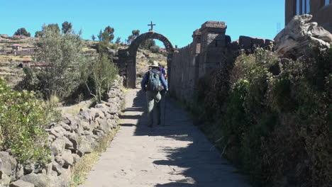 Peru-Taquile-man-walks-path-toward-stone-arch-12
