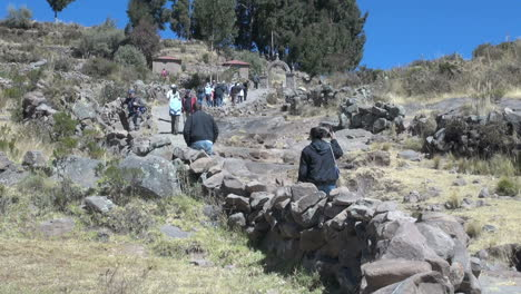 Peru-Taquile-climbing-hill-toward-arch-and-trees-26