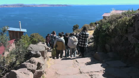 Peru-Taquile-tourists-descend-steps-toward-lake-24